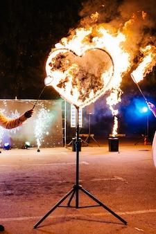 Feuershow, performance und unterhaltung bei nacht. designelement liebe. freier platz für text. erstaunliche feuershow in der nacht auf einem festival oder einer hochzeitsfeier. happy valentinstag postkarte. hochzeitskonzept.