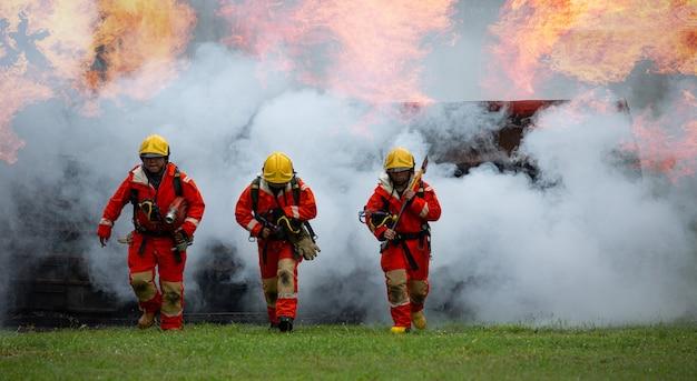 Feuerteam bereitet ausrüstung für maßnahmen vor, um schadensexplosionsfeuer und -rauch zu schützen. teamwork-held läuft und geht mit besatzung.