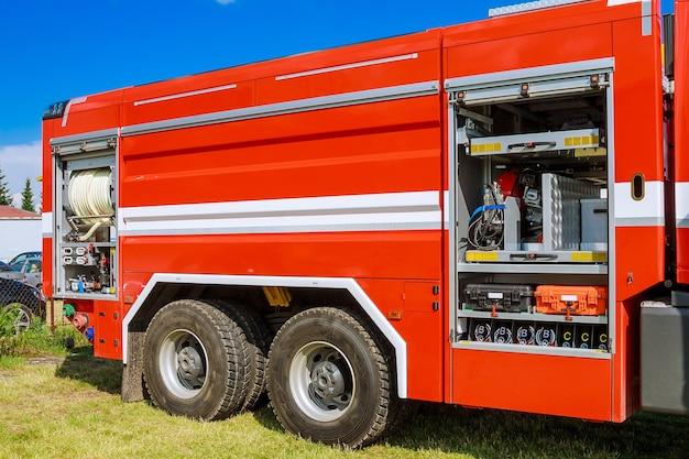 Feuerwehrausrüstung in einem lkw. seitenansicht des roten städtischen feuerwehrautos, das im leerlauf steht.