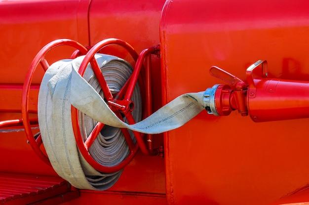 Feuerwehrauto mit feuerwehrschlauch. seitenansicht des roten städtischen feuerwehrautos, das im leerlauf steht.