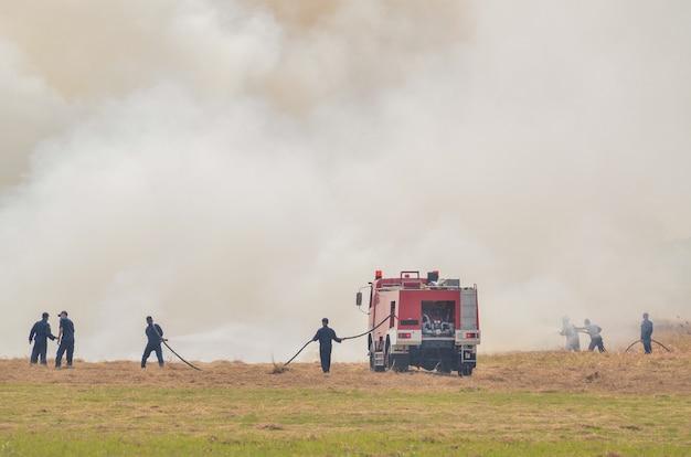 Feuerwehrleute arbeiten daran, brände auf den feldern zu löschen, die viel weißen rauch haben.