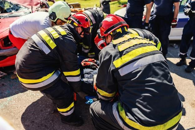Feuerwehrleute kümmern sich um andere feuerwehrleute und ziehen ihn aus einem verunglückten auto.