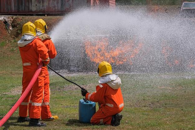 Feuerwehrleute löschen das feuer mit einem chemischen schaum, der durch einen langen schlauch vom feuerwehrauto kommt.