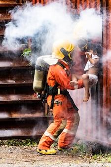 Feuerwehrleute retten ein kind mit rauch aus dem gebäude