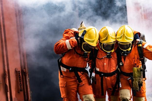 Feuerwehrleute retten einen kollegen aus dem gebäude mit rauch