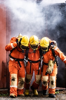 Feuerwehrleute retten einen kollegen vor dem verbrennen von gebäuden mit rauch