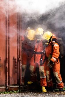 Feuerwehrleute retten kollegen aus dem gebäude mit rauch