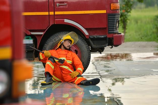 Feuerwehrleute sitzen erschöpft, um sich auszuruhen, nachdem sie den opfern des feuers geholfen haben.