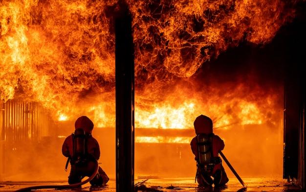 Feuerwehrleute sprühen nachts flammen nieder