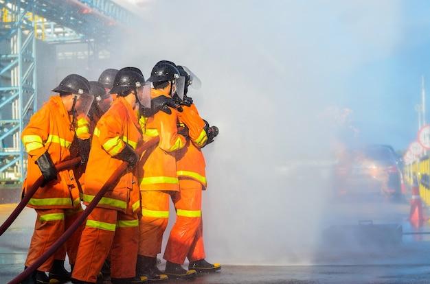 Feuerwehrleute sprühen wasser für feuerübungen in industrieanlagen.