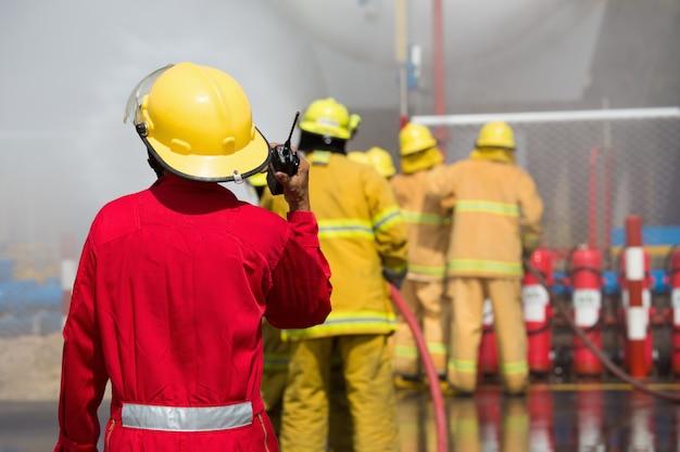 Feuerwehrleute sprühen wasser in feuerlöschern durch explosives gas