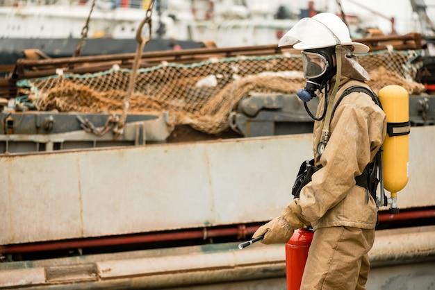 Feuerwehrleute verwenden feuerlöscher, um die flammen im seehafen zu löschen