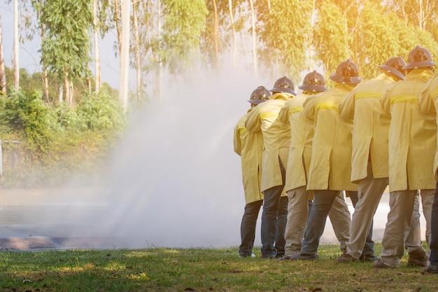 Feuerwehrleute verwenden feuerlöscher und wasser aus dem schlauch zur brandbekämpfung