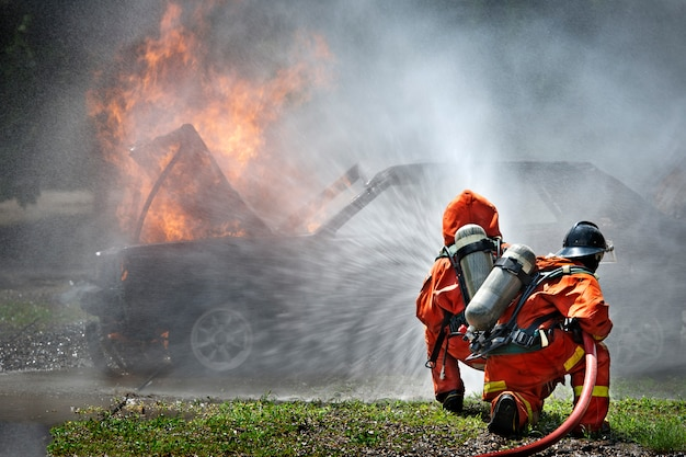 Feuerwehrleute verwenden feuerlöscher und wasser für das feuer der kämpfer während des feuerwehrtrainings.