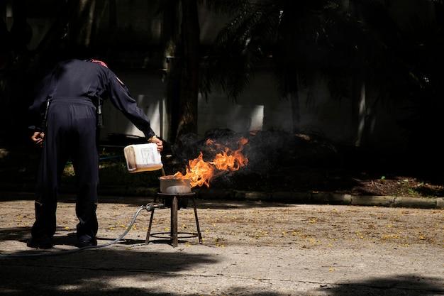 Feuerwehrleute zeigen die hitze einer flamme und den einsatz von feuerlöschern.