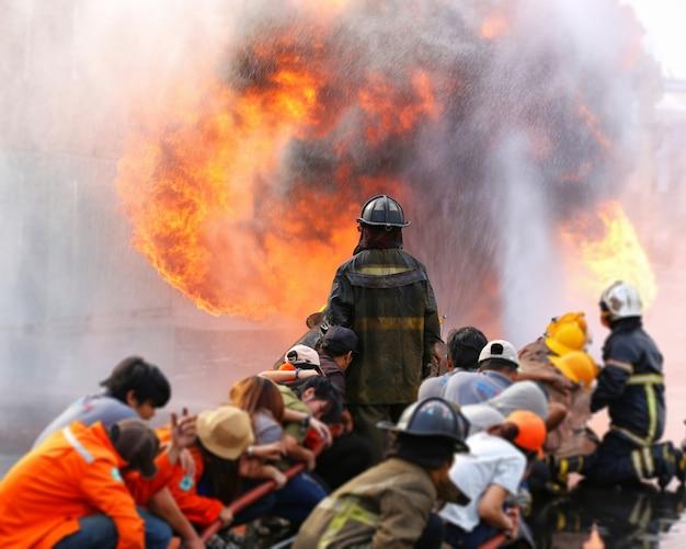 Feuerwehrmänner, die feuer während des trainings mit arbeitskraft kämpfen