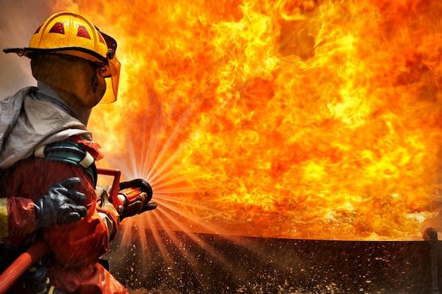 Feuerwehrmänner, die feuerlöscher und wasser vom schlauch für feuerbekämpfung am feuergefechtstraining verwenden