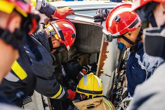 Feuerwehrmänner, die versuchen, einen in einem auto gestapelten mann freizulassen