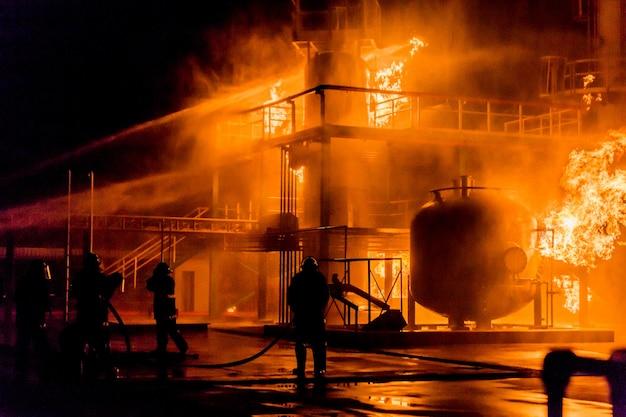 Feuerwehrmänner, die wasser vom schlauch für feuerbekämpfung am feuerwehrentraining der versicherungsgruppe verwenden
