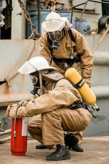 Feuerwehrmänner überprüfen die ausrüstung und den feuerlöscher auf einem training, wie man feuer im seehafen stoppt
