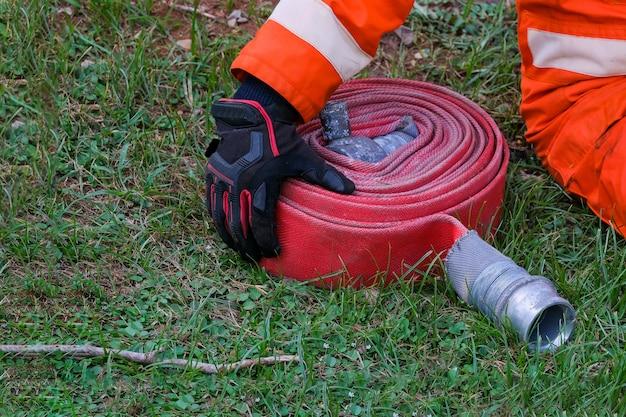 Feuerwehrmänner und feuerwehrschlauch spulen regelmäßig feuerwehr- und rettungsschulung, um sich fertig zu machen - hilfe, brandschutzkonzept