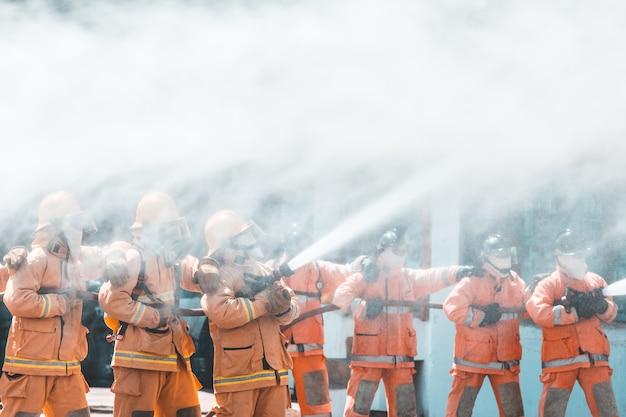 Feuerwehrmann benutzt wasser und feuerlöscher, um mit feuerflamme zu kämpfen