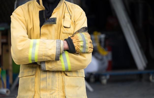 Feuerwehrmann crossarmperson, die versuchen, feuer durch feuerlöscher im feuergefecht zu stoppen.