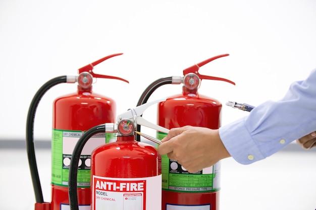 Feuerwehrmann, der den füllstand des manometers des feuerlöschers überprüft.