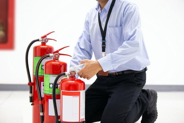 Feuerwehrmann, der den griff des roten feuerlöschers überprüft.