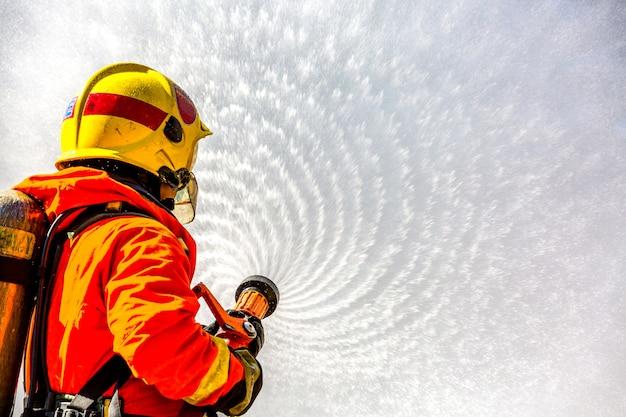 Feuerwehrmann, der feuerlöscher und wasser vom schlauch für feuerbekämpfung verwendet