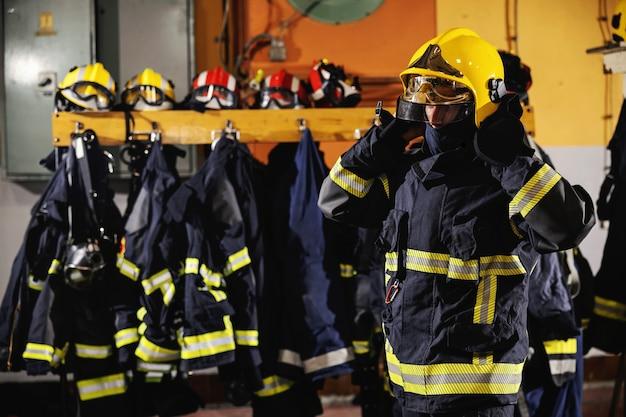 Feuerwehrmann, der in der feuerwache steht, helm setzt und sich auf aktion vorbereitet.