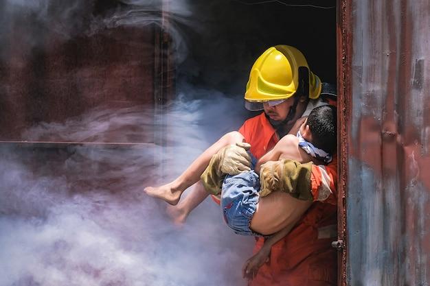 Feuerwehrmann, der kinderjungen hält, um ihn im feuer und im rauche zu retten
