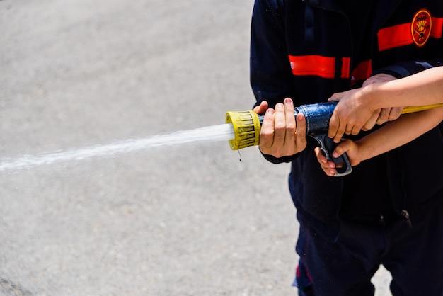 Feuerwehrmann, der kindern während einer anzeige zeigt, wie man einen wasserschlauch benutzt