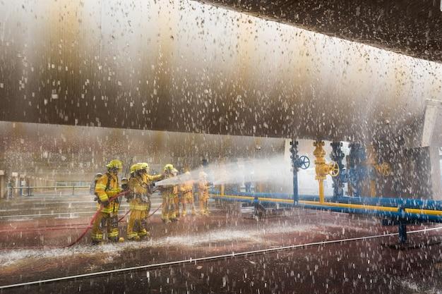 Feuerwehrmann, der zeigt, wie man sprinkler benutzt. auf ein trainingsfeuer