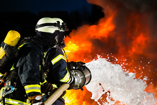 Feuerwehrmann, feuerwehrmänner, die eine große flamme löschen