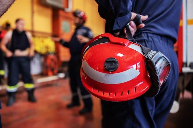 Feuerwehrmann hält helm und hört einem chef zu. boss spricht über taktik, wie man sich um feuer kümmert.
