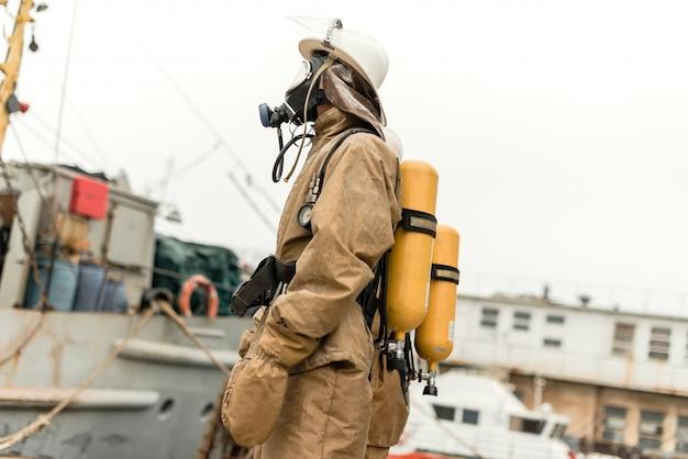Feuerwehrmann im seehafen mit ausrüstung auf einem training, wie man feuer stoppt