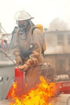Feuerwehrmann löscht feuer mit einem feuerlöscher