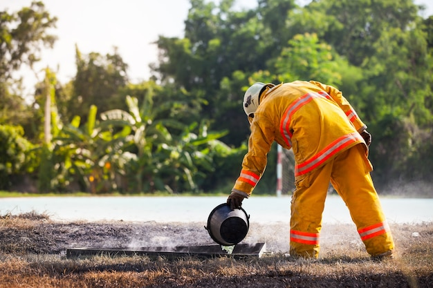 Feuerwehrmann mit feuer und anzug zum schutz des feuerwehrmannes für die ausbildung von feuerwehrleuten.