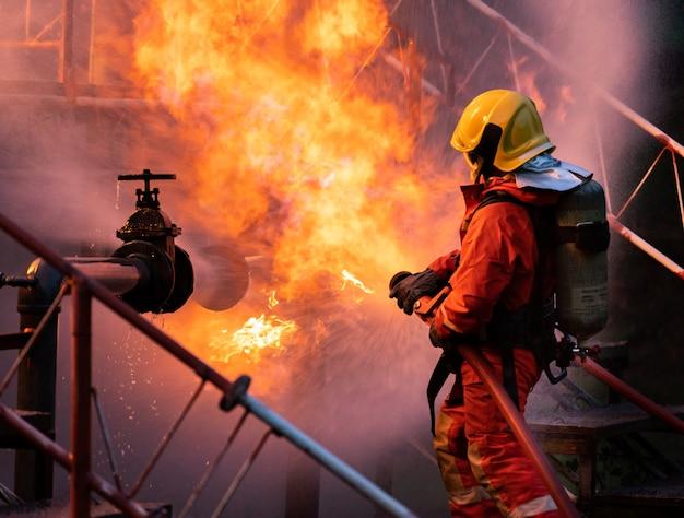 Feuerwehrmann mit feuerlöscher vom typ wassernebel zur bekämpfung der feuerflamme durch leckage und explosion der ölleitung auf der bohrinsel und der erdgastankstelle. feuerwehrmann- und arbeitsschutzkonzept.