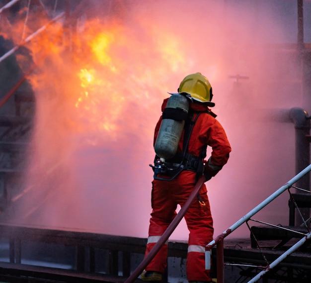 Feuerwehrmann mit wassernebel feuerlöscher zur bekämpfung der feuerflamme