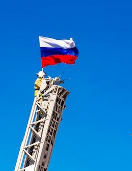 Feuerwehrmann sichert eine russische flagge auf feuerleiter auf blauem himmel