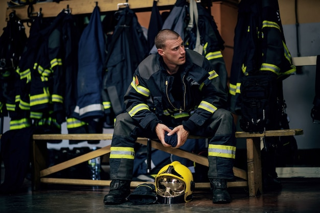Feuerwehrmann sitzt in der feuerwache und wartet auf andere feuerwehrmänner