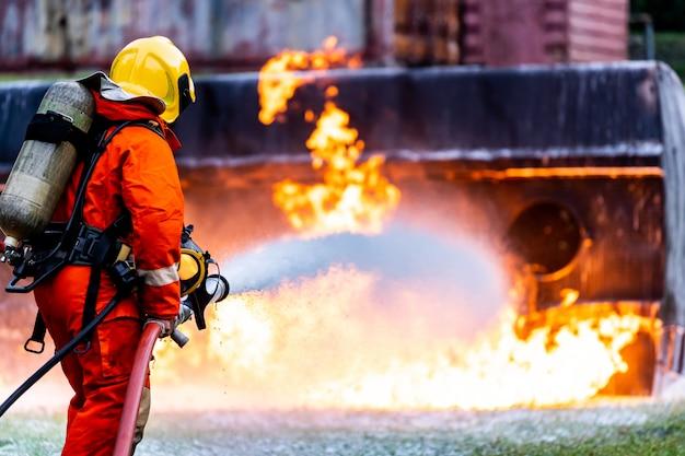 Feuerwehrmann sprüht feuer von öltankwagenunfall