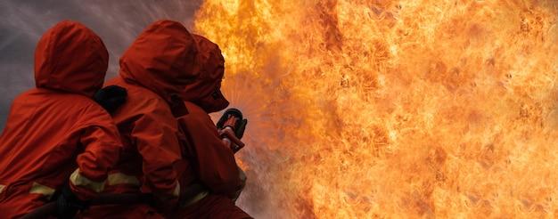 Feuerwehrmann stoppen brennende flamme des gebäudes.