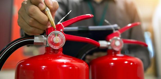 Feuerwehrmann überprüft feuerlöschertank im gebäude.