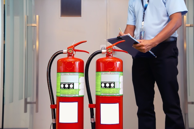 Feuerwehrmann überprüft feuerlöschertank im gebäude