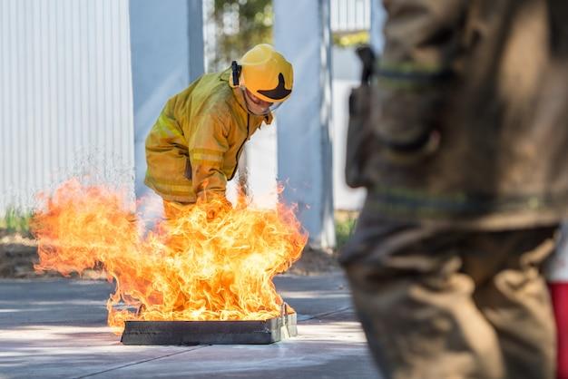 Feuerwehrmann zeigt einen feuerlöscher an einem trainierenden hydranten mit weißem rauch. arbeitsschutzkonzept.