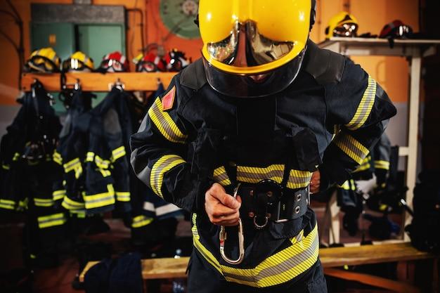Feuerwehrmann zieht schutzuniform an und bereitet sich auf die aktion vor, während er in der feuerwache steht