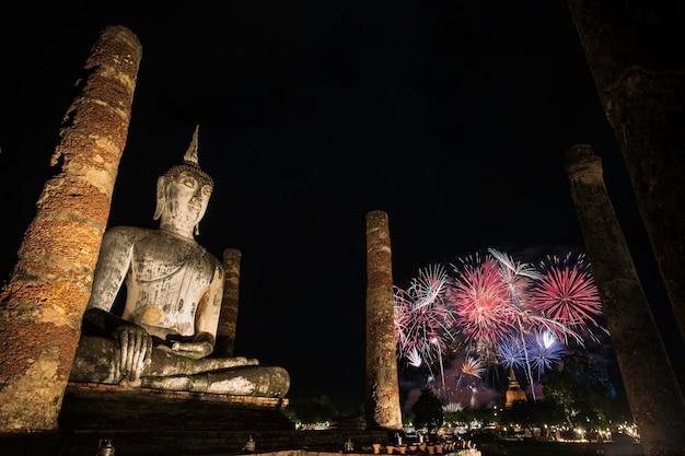 Feuerwerksbuddha im sukhothai historical park während des loy krathong light and candle festivals, wat mahathat tempel im bezirk des sukhothai historical park Premium Fotos